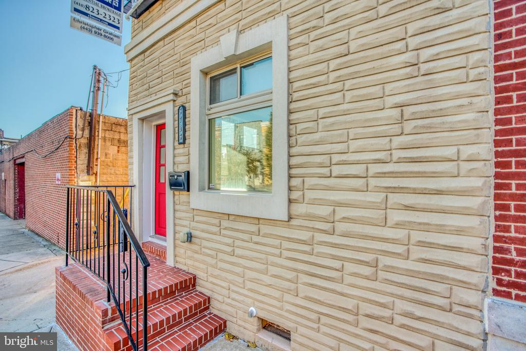 """WOW! PRICE REDUCED! Stunning and unique updated end-unit on the best block in Highlandtown with 3 car tandem parking and second level Trex deck.  This home has a custom metal staircase with landing, stainless appliances in kitchen, half bath on main level,  new paint throughout, and gleaming wood floors. The newly waterproofed and finished tall basement makes great family room with exterior access, lots of storage and another half bath... one of the best basements I've seen in a city row home!  New roof and carpet on upper level and basement level, too . Each of the large two master bedrooms has a full bath, and master suite leads to wonderful rear deck.  Completely original and an absolute must-see this home was  once the """"United Democratic Club"""" Founded in 1922!"""