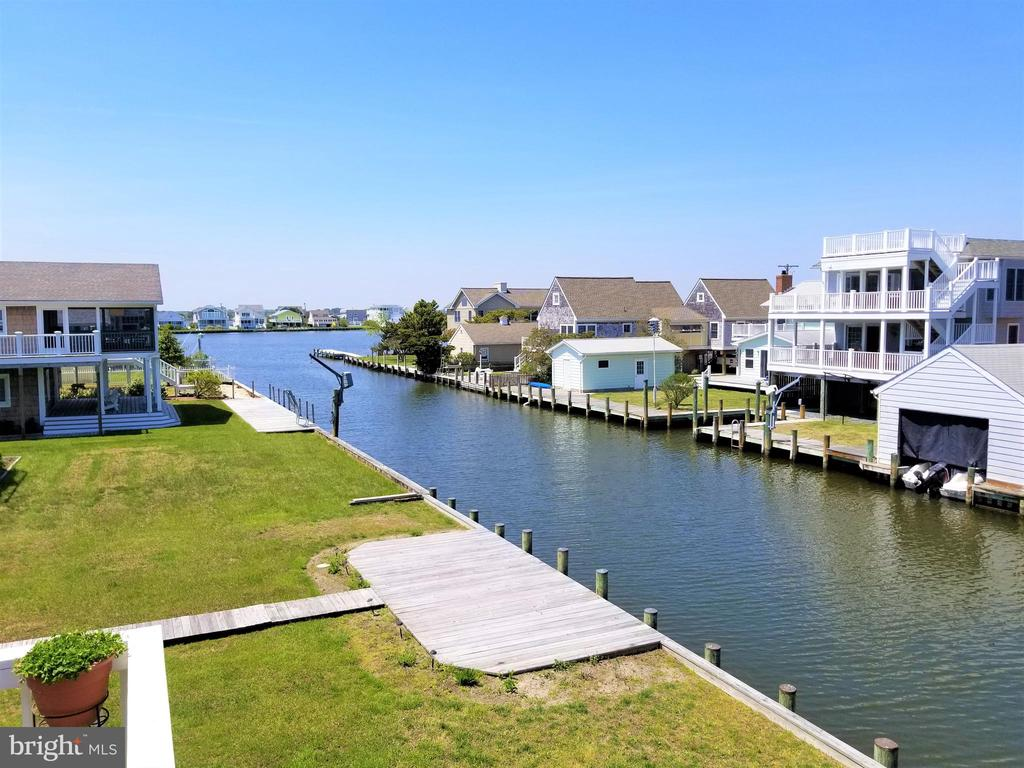 MOTIVATED SELLER! WILL CONSIDER ALL OFFERS! JUST REDUCED!  Best Water & Canal Views in Fenwick Island! This Custom Built home overlooks the canal with water views of the Assawoman Bay.  Home features 4 spacious bedrooms (2 Master Bedrooms) & 3.5 Baths. Main level Master includes private screened porch and an over-sized Jacuzzi tub  in the bathroom. Relax outside with 5 Outside Decks to choose from (2 screened).  Brand new laminate flooring throughout main level (15yr warranty).  Brand new roof and new hurricane proof screens on outside enclosed decks. Parking for 8-10 vehicles. A very short walk to beach, shopping, restaurants, churches, town hall, miniature golf and water parks.  A Must See! Water Lover's Dream Home!