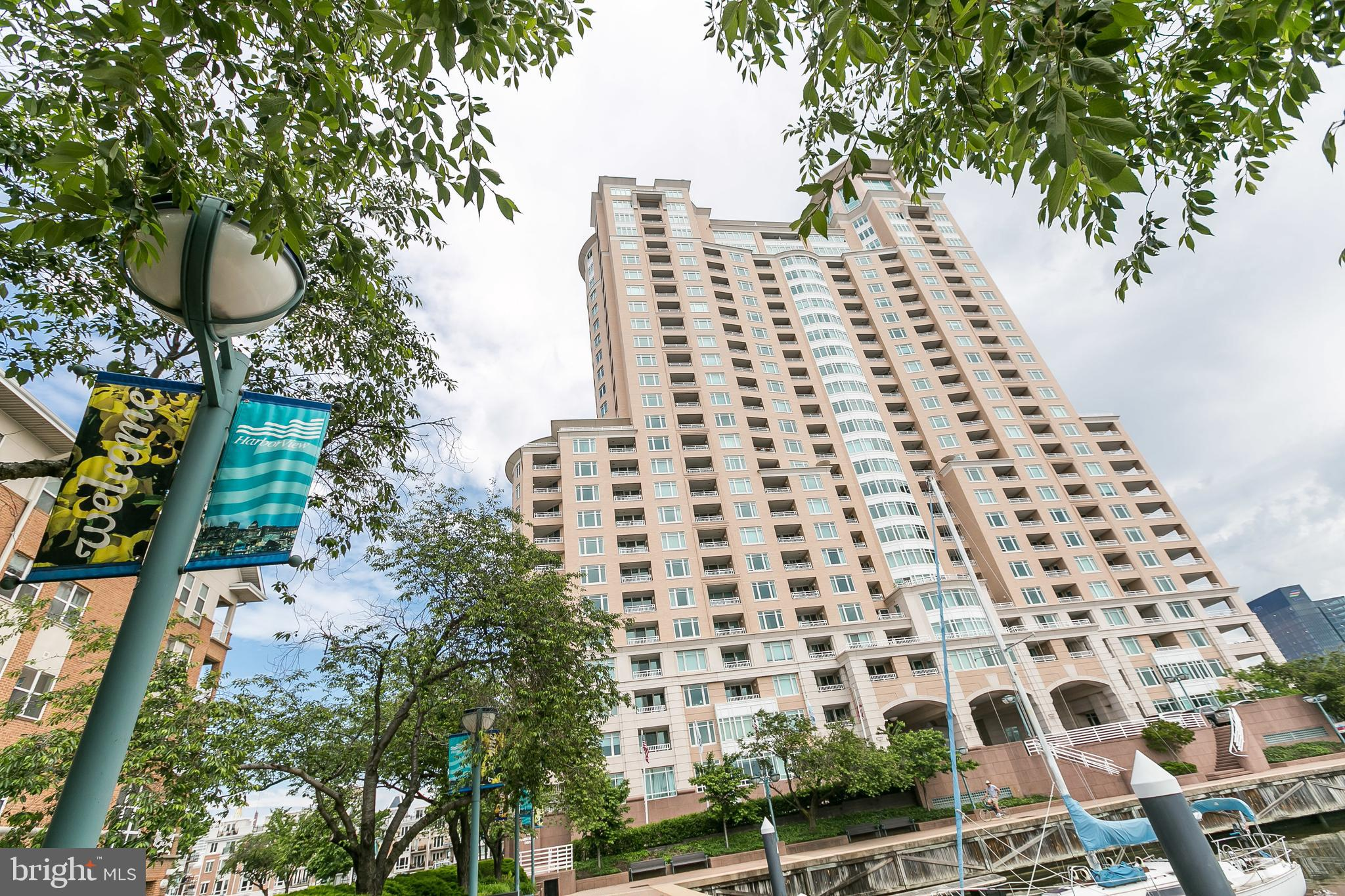 Capture the essence of city life with Spectacular views of both Inner Harbor excitement and the serene setting of the Harborview Marina from this 1,664 sf beautifully designed floor plan.  French door entryway opens to marble foyer. Spacious living room and formal dining room offer warm hardwood floors leading to slider to balcony - comfortable for year-round outdoor entertaining. Formal dining area with private balcony entrance and bay windows offering lots of sunlight and views of both stadiums, Fed Hill, Baltimore Aquarium, Pier Six Concert Pavilion, Harbor East, Harbor Point and the Inner Harbor Gateway! Enjoy early mornings in the quiet breakfast area beside the gourmet kitchen. Fine quality kitchen features include recessed lighting, granite counters, durable cabinetry with crown molding, cooktop, decorative white tile backsplash, double bowl sink, side by side fridge, microwave and double ovens. In the Master Suite and second bedroom you'll find comfortable neutral tone Berber carpet in classic pattern matching the small print bedroom curtains. Other features include recessed accent lighting, spacious walk-in closet and 2nd balcony access. Private Master Bath with double bowl marble vanity, marble floors, whirlpool tub and separate walk-in shower. Second bedroom with neutral tone Berber carpet, also with classic pattern, double door closet and 2nd balcony access with views of Domino Sugar, Port Covington and the South Baltimore landscape, Key Bridge and beyond! Quality decorator wallpaper accents throughout. Living in such luxury, also enjoy 2 assigned garage parking spaces, as well as the many building amenities and services at your fingertips. 24/7 front desk concierge, gated garage parking, beautifully landscaped grounds with water fountains and walking/jogging paths, extensive fitness center, steam/sauna, in & outdoor pools, valet guest parking, social lounge, billiard room, conference room, business center, ballroom, bike storage, grill area, onsite gues