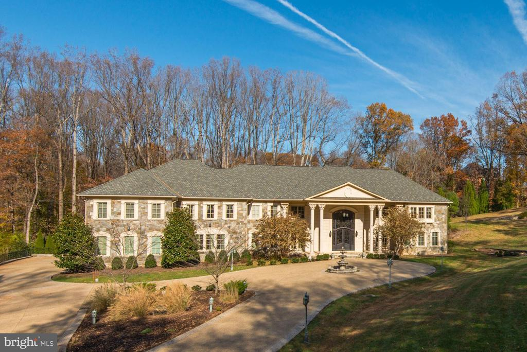 Feel the pride of calling this regal estate home as you approach via a long, tree-lined drive that circles at the entry. Grand Corinthian columns on either side of wide steps support the stone masonry exterior. This 20,000 square foot home with 7 bedrooms, 7++ baths offers an extraordinary luxury lifestyle amidst a serene surrounding landscape. Custom double doors of glass and iron open to a magnificent, yet welcoming marble-floored reception hall. Upon entering, sleek marble flooring leads you to a formal living on the right and dining room on the left, perfect for accommodating guests. A few steps in reveal a stunningly bright great room:  floor to ceiling windows with 3 sets of French doors provide a sun-drenched space from the rich hardwood floors to the coffered ceiling and crystal chandeliers two stories overhead. Master chefs and amateur cooks alike will treasure the simple elegance and thoughtful design of the bright gourmet kitchen stretching the entire width of the home. A professional Wolf range with 8 burners, a griddle and dual ovens serves as centerpiece amidst wrap-around granite countertops and two beautifully finished, expansive islands. Ivory-hued cabinetry and two corner china cabinets provide ample storage. A separate breakfast area on one end complements the bar seating along either island. The opposite end of the room features a large informal dining area that opens via French doors to the rear deck. Among the bedrooms upstairs is the impressive Master Suite. Rich hardwood floors stretch from the master suite foyer with morning kitchen, to a lovely sleeping area, and separate a sitting room with corner gas fireplace. Tiered, tray ceilings with generous crown moldings, and recessed lighting create comfortable elegance. The suite extends into the huge marbled bath complete with a his and her steam shower, relaxing Jacuzzi bathtub, his and her vanities, and two separate water closets. Generous his/her walk-in dressing room/closets with dark wood built-ins complete the suite. This level offers four additional bedrooms suites, each with walk-in closet and unique updated bath, along with a large laundry room and open family room. A large finished space on the 2nd upper level can be used as playroom, studio or office.Additional features of the home include a professional office/library with outside access, separate music/receiving room, wrap around deck in the rear of the house, private Mediterranean terrace with retaining wall, main level bedroom suite, a posh 18-seat home cinema, glass-enclosed fitness room, spa suite with steam room and shower, security system, elevator, and a well-equipped wet bar.  In addition, the scenic and beautifully landscaped lot stretches 3.6 acres for ultimate serenity and privacy. The overall layout of the home is open and bright, creating a luxuriously welcoming and elegant atmosphere for family and guests.