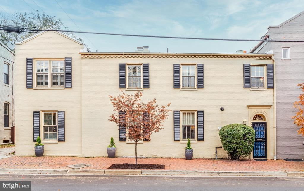 """This unique historic property built in 1800 was formerly a store and has been transformed into a beautiful 2 level home.  Fabulous location just 2 blocks off historic King St. and a short stroll to King St. METRO, the waterfront, shopping and restaurants!  Foyer entry with original brick floors welcomes you to the living room and dining room with a gas fireplace and custom built-ins.  Gourmet kitchen with SS appliances, beautiful 42"""" natural Maple cabinetry, granite counters and breakfast bar.  Adjoining family room with glass doors to a charming walled patio... perfect for grilling and al fresco dining!  Upper level den with gas fireplace and 2 bedroom suites including the Owner's suite with a balcony.  The en suite bath features a marble topped vanity & floors and large walk-in shower with a built-in seat.  Upper laundry, main level half bath, abundant closet space with organizers, double paned Pella replacement windows and sliding doors.    Off Street Parking!"""