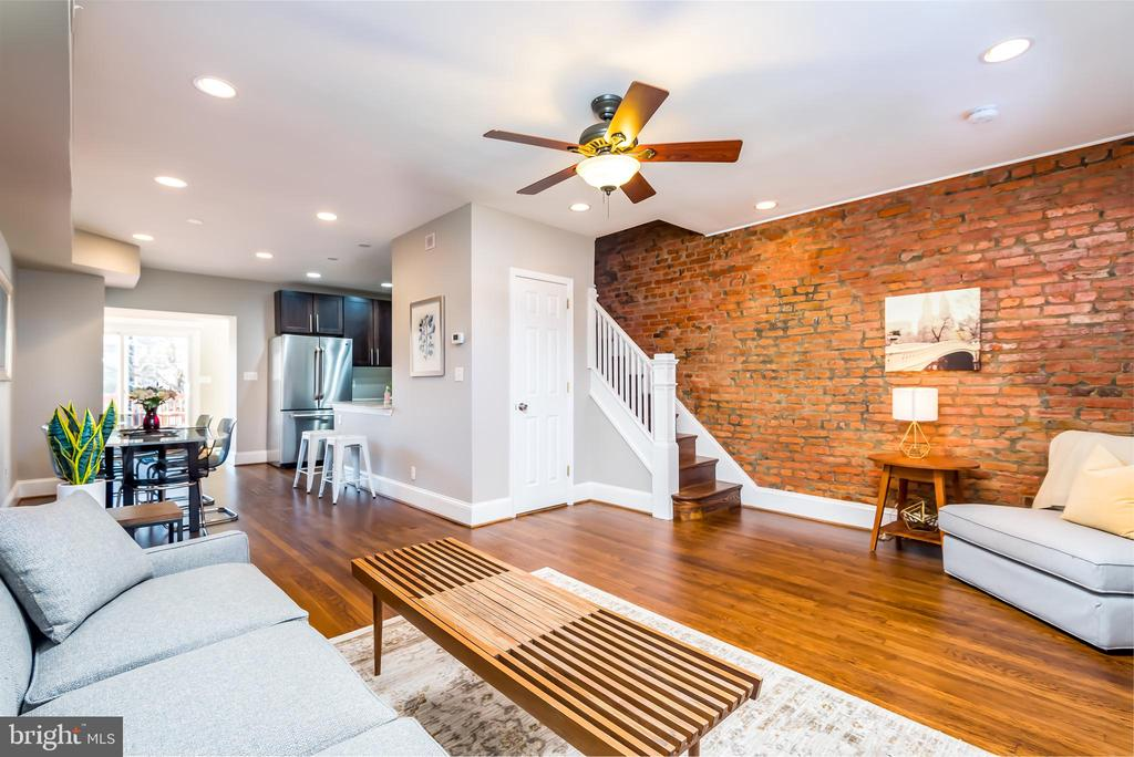 OPEN SUN 12/15 2-4pm. Beautiful 3 BR + Den, 2.5 BA, 3-Level open concept Brookland Townhouse w/ over 1,800 sq ft of finished living space.  The home underwent a total gut Renovation completed in 2011. Amazing private outdoor space with secure, tandem parking spaces for 2 cars,  a fully-fenced front yard and front porch, and privacy-fenced back yard and spacious deck w/ walk down stairs. Main level features refinished oak hardwoods throughout with an inviting front entertaining Living room, Kitchen with gas cooking, rich cabinets + a breakfast bar, dining table space for parties, and a bonus, light-filled multipurpose room that can be used to watch Netflix or as a home office / playroom area. The historic townhouse feel is captured by the exposed brick feature wall that highlights the space. A powder room was added for convenience, ensuring a restroom is included on all three levels. 3 Bedrooms are found upstairs with a full bathroom containing a jacuzzi tub and custom inserts in the Master and 2nd BR closets to maximize clothes storage. The walkout basement features a private, rear entrance from a covered patio leading to the sizable Den with enough space to function as a NTC 4th BR for guests across from another full bathroom with standup shower and laundry area. The hallway from the den opens into a  lower-level rec room with good ceiling height and a functional layout, with new, durable engineered flooring found throughout the lower-level.  Gas Furnace and Gas Water Heater. Central A/C and recessed lighting on every level and electric alarm wired w/ motion sensors. Extra storage can be found under the stairs. Located in the shadow of Catholic University's campus and walking distance to Rhode Island Ave Metro, enjoy the multitude of Brookland restaurants and local activities nearby.
