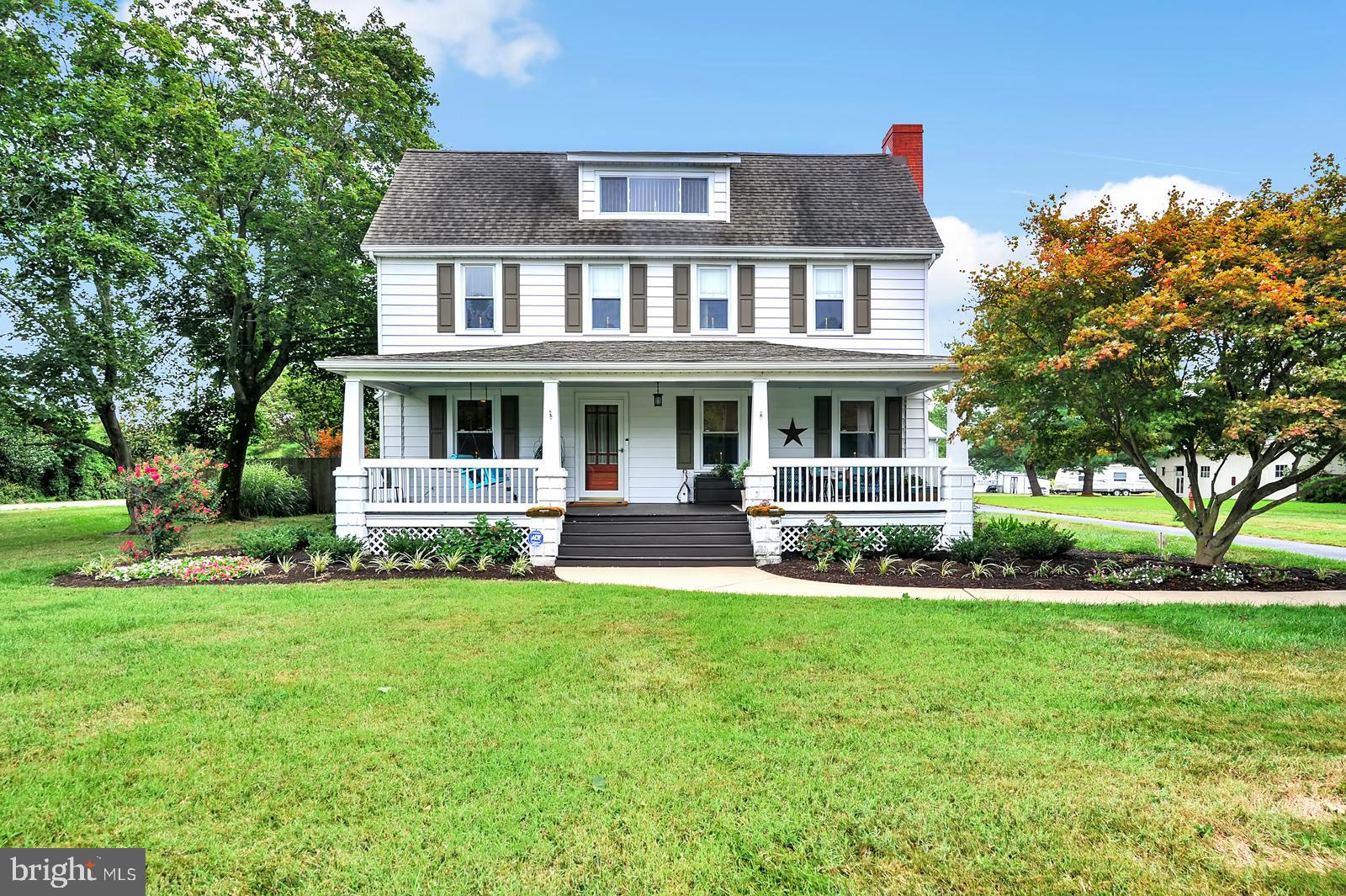 This beautiful American foursquare historic home is the absolute picture of perfection. The utmost care has been taken with this home, and pride of ownership shines throughout.  Step up onto the gorgeous 35' x 9' front porch and imagine mornings gazing out across the fields, or evenings rocking away, admiring the newly landscaped lawn.  Upon entry, you'll be greeted with recently updated carpets, beautiful historic colors throughout, and original trim, all specially restored and replaced to its original location. The living room, complete with original fireplace, boasts original hardwood flooring, sanded and refinished for a brand new look, and original french doors leading into the formal dining area. The gourmet kitchen, renovated just a few years ago, boasts hard-surface countertops, custom backsplash, newer appliances, and a peninsula with an informal seating area for all of your entertainment needs. The original canning kitchen allows for even more seating area, should it be needed, plus has been renovated into a main floor laundry area complete with built in utility closet/storage cabinets. Rounding out the main floor is the first of four bedrooms, currently being used as an office, which connects to the main floor, fully renovated bathroom, but would make an ideal bedroom for anyone in need of first floor living! Upstairs, you will find three overly spacious bedrooms, including the master connecting to the sewing room, which provides accessibility to the partially finished attic space, and another fully renovated bath with amazing custom-tile shower, modern flooring, custom wood vanity with solid surface countertop and dedicated makeup area, built-in wooden linen closet, and two skylights (crank opening!) to provide all of the natural lighting and air you could desire! Should you be in need of storage, there is a full, dry basement in addition to the attic space that was once used as living space, plus not one, but TWO outbuildings! The first, a 3-car garage,