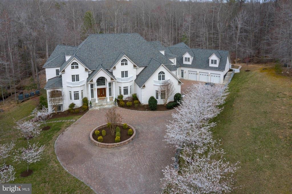 Tucked peacefully off Woodland Hills Lane, you will discover a private drive framed by lighted brick pillars and a wrought-iron gate that opens to this beautiful, custom estate. The elegant paver driveway crosses over a stream and leads to the tasteful architectural styling and quality brick construction of this estate home. With views of the nearby pond and the large wooded lot, it becomes evident at your first impression that this home is something very special! You will be amazed at 9 bedrooms, 9 full and 3 half baths, 6-fireplaces, an elevator to all four levels, two 3-car garages and one with guest quarters, plus a pool house! This exceptional property is nestled amongst 5-acres of lush Virginia hardwood trees and professionally landscaped grounds with a huge stone patio with an outdoor kitchen, an open brick wood-burning fireplace and staircase to the fire pit, playground area and private yard. There's over 13,000 square feet of quality designed living space with architecturally impressive designed rooms, this home offers something special for everyone!