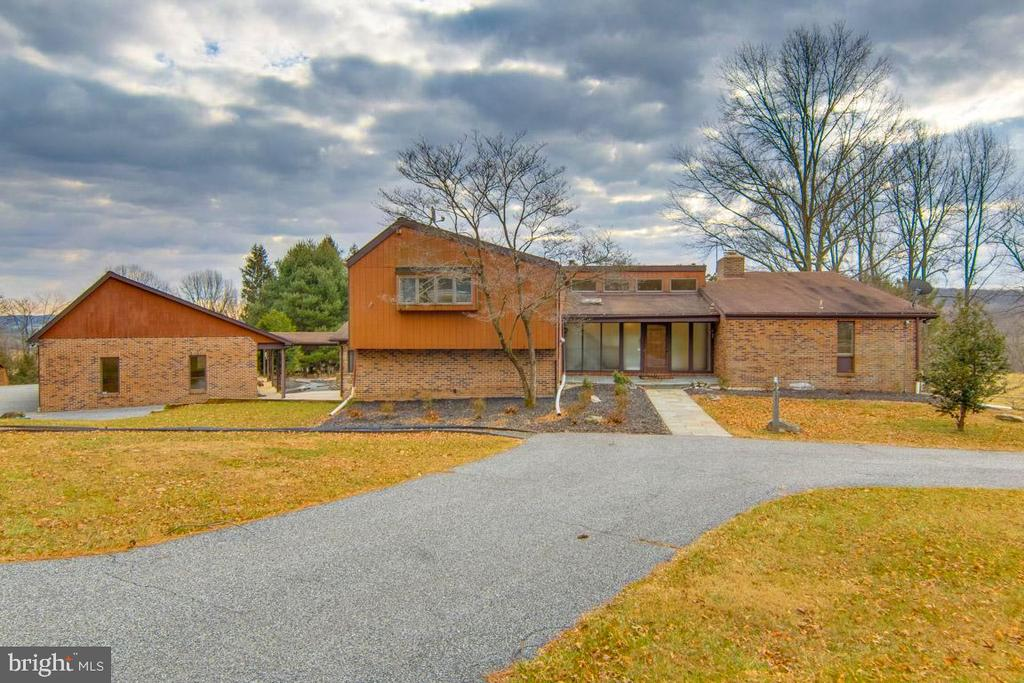 This outstanding contemporary has a beautiful setting on 3.4 acres-the house sets back off of the road.  The entrance foyer overlooks the large living room with the wood burning fireplace and sliders to the large deck- The first floor has wood floors throughout and vaulted ceilings.  The dining room is elegant and large enough for your best furniture-There is a family room off of the kitchen with a half bath that could easily be an office or sitting room. The kitchen has a large island, tons of cabinets, granite counters, built in microwave, trash compactor, dishwasher, warming drawer, bar fridge in the bar area, huge refrigerator-there is also a computer/desk area for your personal use, the laundry room is just off of the kitchen as well.  Off of the kitchen is a gorgeous natural wood sunroom with vaulted ceilings, heated floors, electric skylights, and a  gas fired stove- The sliders take you to the back deck or to the Huge over sized garage-Three car bays plus a workshop place-this garage will handle your largest SUV vehicle. In the garage is water, electricity and heat- Back to the first floor to the master suite-large bedroom, wood floors, walk in california closet, double sink vanity and soaking tub-Great natural light and a fireplace accent this room.  Upstairs there are 4 bedrooms and 2 full baths-carpet, large closets, and a lot of natural light as well. The upstairs master has a private bath with separate shower and soaking tub- The lower level off of the kitchen has one finished room with carpet that could be an office space or second family room, then down a few steps to a finished walk out basement area with tile flooring and full bath-so if you wanted to install a pool this could be a great changing area.  This lovely home is bright, well maintained, and has a gorgeous setting for you to enjoy any season of the year.  The circular driveway brings your guests right to the front bluestone patio porch.