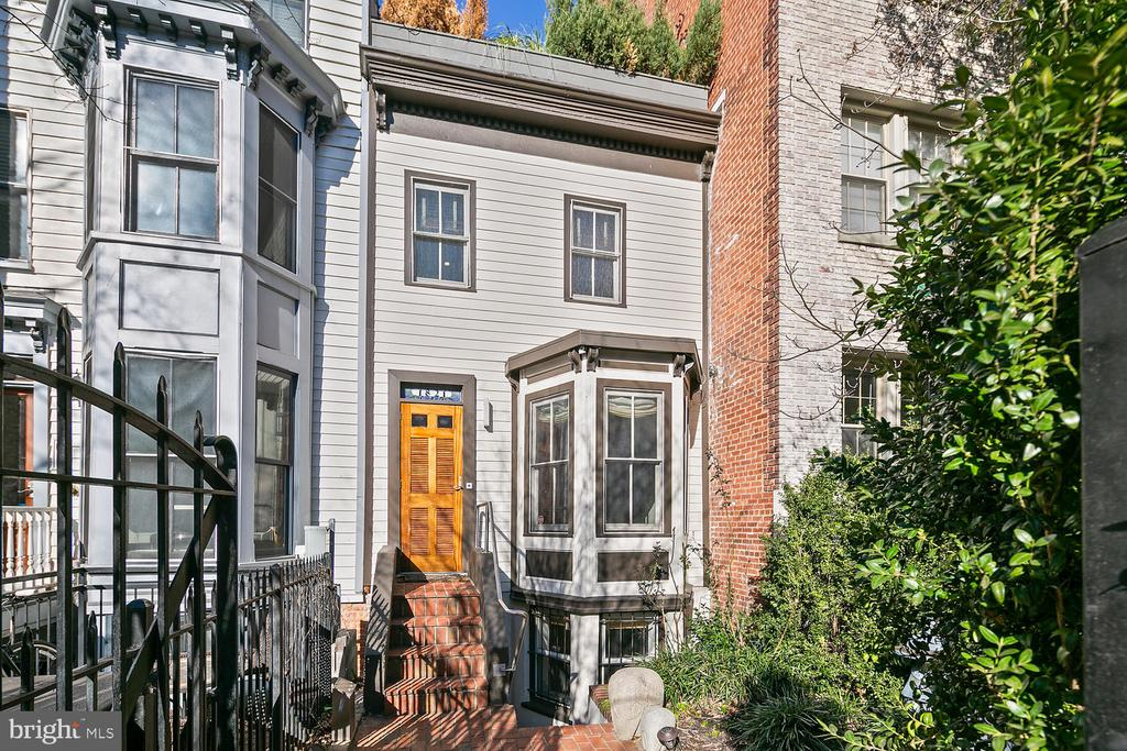 """OPEN HOUSE: SUNDAY 8/9 from 2-4PM. A truly special home. The Clark House, named for prominent DC """"plasterer"""" William H. Clark, is one of the only remaining structures from a group of frame row houses constructed prior to 1877, and is now the oldest building in the block. The current owner lovingly restored this historic home and completed a total luxury renovation in 2001, which was featured on HGTV's 'Before & After' and included many high end features. Main level open floor plan with double-sided fireplace and bay windows. True gourmet chef's kitchen with Poliform cabinetry, Silestone counters, and deluxe stainless steel appliances, including Subzero fridge and Viking gas range. 2nd floor boasts a comfortable lounge with dramatic staircase and 2 story wall of windows that flood the space with natural light. Top floor master suite featuring luxurious ensuite bath with large Kohler soaking tub and steam shower, and a fabulous roof terrace with tranquil garden - the perfect private oasis. Separate lower level apartment includes an additional living room, full kitchen, laundry, bath and bedroom, and makes for an ideal rental opportunity. Front and rear gardens for additional outdoor enjoyment. Separate rear garage with GarageTech system, attic and covered parking provides tons of storage and convenience. Prime location in vibrant Dupont, DC's most walkable neighborhood. Surrounded by epic architecture, convenient to everything, but nestled on a quiet residential street. Explore an endless variety of cafes, restaurants and bars on 18th Street in Adams Morgan, U Street corridor and trendy 14th Street. 3 blocks to Mint Gym. Enjoy the weekend Farmer's market on Columbia Road and Dupont Circle. Transit oriented location with Metro buses on 18th Street and Metros nearby (0.7mile to Dupont and U St/Cardozo). This really is a one-of-a-kind residence with so much to love!"""