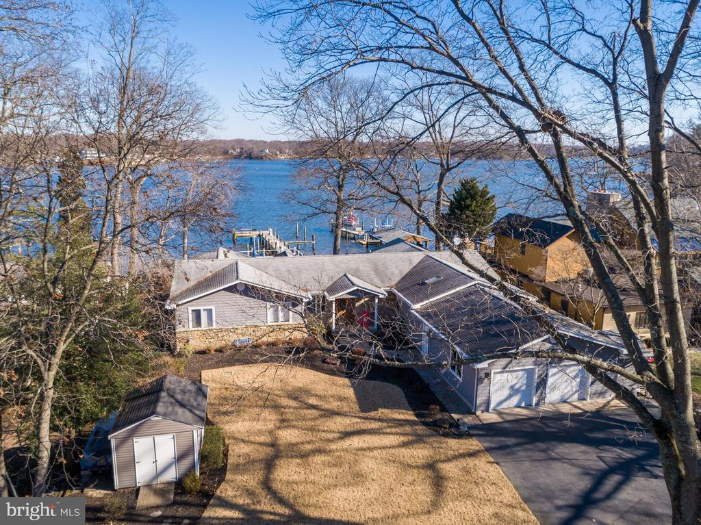 One of a kind waterfront gem on the Magothy.  Spectacular views from nearly every room.  This boater's and entertainer's heaven features 3BR, 2.5BA, a year-round sun room, great room with gas fireplace,  game room, kitchen with granite, stainless steel appliances and cherry cabinets, gleaming hardwood floors throughout, eat-in kitchen, formal dining room, separate laundry room with tub on the main level, 2.5-car attached garage with workshop, basement and crawl space for ample storage....AND a separate guest house (1-BR, 1BA, Liv. Rm., full kitchen and screened-in porch)....all on a half acre.    Severna Park Schools - including Folger McKinsey and Severna Park High...both Blue Ribbon Schools.  Room for 3-5 boats at the dock with 10k lb. boat lift, deep water at the end and floating dinghy dock....all 74 feet rip-rapped.  Dock has 50 amp service and water. The spacious, paved entertainment area leading from the house to the water includes a large space for seating, separate covered patio and a boat shed to store your gear.  The home is perfectly positioned just inside the 6-mile marker...no wake zone immediately off the dock.  Additional features include new Pella windows, irrigation system in the yard and the home is wired for a sound system along with pre-wiring for a whole house generator.  A feature you will not find anywhere else in the county:  12.5 acres of woods that is owned equally by the 15 homeowners in the community.  1/15th ownership of this land transfers with the deed to each homeowner.  Enjoy the water on one side of your home and a permanent wooded view on the other (and around to the side across Arundel Beach Road).  This arrangement was established in 1947, recorded with Anne Arundel County and has remained unchanged since then.  Add it all up and make this unique waterfront mecca your new home.
