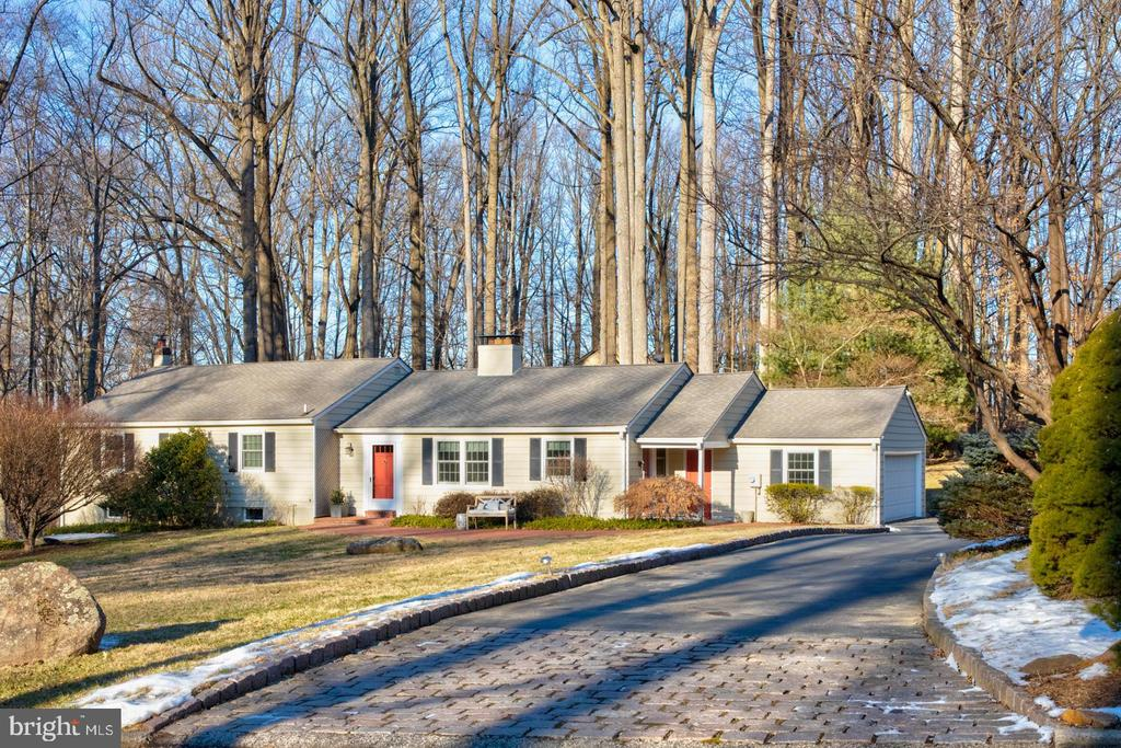 Not too big, not too small, Just Right! Sunny, warm and welcoming, you'll feel right at home in this updated ranch, on a quiet cul-de-sac, nestled on a very private 1.5 acre partially wooded lot.  Four beautiful plum trees line the front of the property bringing color to your spring! Belgian-block driveway accents and a gracefully curved brick front walkway are just some of the special features you'll notice even before entering this lovely home.  Inside, you'll find tasteful updates, custom detailing and special features including built-in cabinetry, hardwood flooring throughout the main level (including all bedrooms),  and a cozy breakfast room that you won't want to leave - with a brick fireplace, glass-front built-in cabinetry and bench seating.  The country-kitchen features glass-inlay pocket doors, creamy white cabinetry with plenty of storage, a gas cook-top, stainless appliances, granite counter-tops and backsplash, and outside access to the covered breezeway.  The great room (combined living/ dining room) is simply stunning with hardwood flooring, a wall of windows,  wood-burning fireplace, and outside exit to the back patio. The dining area features a beautiful chandelier (included), plus custom built-in cabinetry and bench seating.  Two-steps lead up to the bedroom wing, discreetly tucked away from the main living area.  The king-sized master bedroom is large and sunny with a vaulted ceiling, and glass-paned French-style doors that open to a newly-renovated (composite) balcony overlooking the woods and stream.  Perhaps you'd like to enjoy your morning coffee on the balcony, or open the french doors on warm spring and summer nights and listen to the sounds of nature and the babbling stream to lull you to sleep! The luxury Master Suite has three two exposures of light, and features two walk-in closets, both with built-in organizing systems. The en-suite master bath has a double-sink vanity with crema marble counter-tops, travertine tile flooring, a large jetted soaking tub, and over-sized shower.  Bedrooms 2 and 3 also both feature hardwood floors and generous closet space also with built-in organizers. The hall bathroom has a tub/shower combination, tile flooring and tub/shower surround.  Downstairs, the partially finished lower level features a large family room with plenty of room for a large screen TV,  a reading or gaming area and more.  Wainscot accents, built-in shelves and even a gas fireplace make this cozy room even more special.   The adjacent unfinished basement space includes the laundry area, space plumbed for a future powder room, a cedar closet, storage area, and daylight-walk-out exit to the side yard.  The easily accessible crawl space offers additional storage, along with the partially-floored attic.  The attached 2-car garage is accessed from the covered breezeway adjacent to the kitchen.  10 year old roof, many replacement windows, newer stainless appliances (sellers are replacing the dishwasher with a new stainless prior to settlement), and newer central air conditioning.  Sought-after Easttown Township location, top-rated TE school district, and Beaumont elementary school!