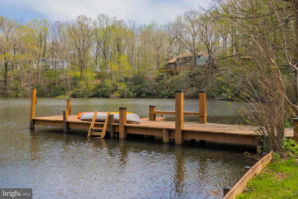 A stunning gem in Northern Virginia, this unique retreat is quietly nestled on an oasis of nearly ten acres, seven of which are a sparkling, private, spring-fed lake! This one-of-a-kind escape was built in 2001 and features 3 bedrooms and 2.5 bathrooms throughout the inviting open living spaces, and boasts beautiful hardwood floors, an abundance of natural light, and striking views of the surrounding woods and lake throughout. One enters the home via a breath-taking glass atrium which offers immediate views of the lake and dock. What is more, entertaining will come easy in the recently renovated kitchen, which boasts beautiful quartzite countertops and stainless-steel appliances, and opens to the magnificent great room featuring a towering stone fireplace, 15 foot ceilings, and 2 sets of French doors opening to the spacious rear deck. The second level hosts three bedrooms with new flooring and two bedrooms, including the master suite, overlooking the lake. A 50-year architectural shingle roof was installed July 2019 and includes a transferable warranty. The exterior serves as an extension of the home, featuring the breathtaking rear deck and beautiful courtyard and garden. A quaint path leads from the relaxing overlook off the garage, down to the private dock to enjoy countless hours of kayaking, canoeing, fishing, or bird-watching. The home is completed with a two-car garage accessed via a charming breezeway. This exciting property offers unmatched convenience, and is only 1.75 miles to Great Falls Village, 4.5 miles to Tysons Corner, and 10 miles to Washington DC.