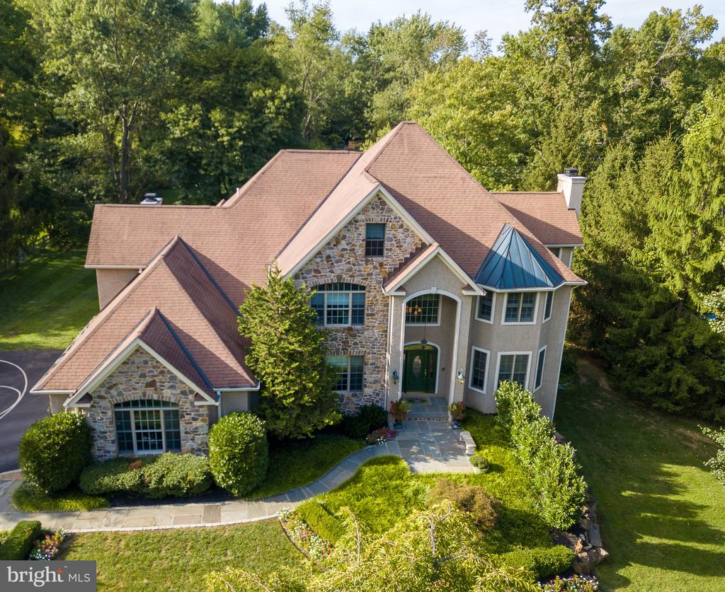 We have 3D Matterport and Video Tours available for this property! Welcome to 521 Sugartown Road - a spectacular custom stone colonial home offering 5 bedrooms and 5.1 bathrooms situated on a magnificent one acre lot in the heart of Devon and Top-Rated Tredyffrin-Easttown School District. Architectural features and exquisite detail abound in this elegant home such as extensive millwork and wainscoting, keystone peaked archways, rounded wall corners, and transom and oval windows. The grand entrance of this breathtaking home offers a dramatic two-story foyer with a sweeping staircase and gleaming mahogany hardwood flooring. From the formal living room to the spacious dining room with attached parlor/sunroom with marble surround gas fireplace, this home is an entertainer's dream!  The large and upgraded gourmet kitchen with attached breakfast room opens to the focal point of the home - the two-story great room - featuring rustic wood ceiling trusses and a floor-to-ceiling stone wood burning fireplace with an impressive wood mantle. The main level is completed with a professional style office with cherry built-ins and wainscoting, a powder room, and the recently expanded mudroom with five built-in lockers, cherry hutch/desk, charging station, and cabinets.  The second level offers an incredible master bedroom suite with sitting area with gas fireplace; master bathroom with his and her vanities, soaking tub, and large stall shower; and a massive walk-in closet with built-ins and vanity/make-up area.  Three additional bedrooms all with large closets and two full bathrooms, complete the second floor. The third level of this amazing home features a fifth bedroom with high ceilings, walk in closets with built-in cabinetry, and a full bathroom. The finished, walk-out basement is bright and open and offers an additional bedroom/bonus room, full bathroom and a recently updated laundry area with two sets of washers and dryers, sink area with cabinetry and custom shelving.  The professionally landscaped grounds of this property are not to be missed - enhanced stone and slate entrances and walkways, high-end lighting, estate gate and fencing, and amazing outdoor living spaces.  Featuring an expansive slate patio, cedar pergola, and upper deck connecting to the great room and breakfast room- indoor/outdoor entertaining has never been so easy! Close to Devon Yard, the Devon Horse Show, minutes to downtown Wayne with it~s amazing array of dining and shopping options, minutes to the Paoli train station, and convenient to all major roadways for an easy commute to Philadelphia and Wilmington.  This home is not to be missed!