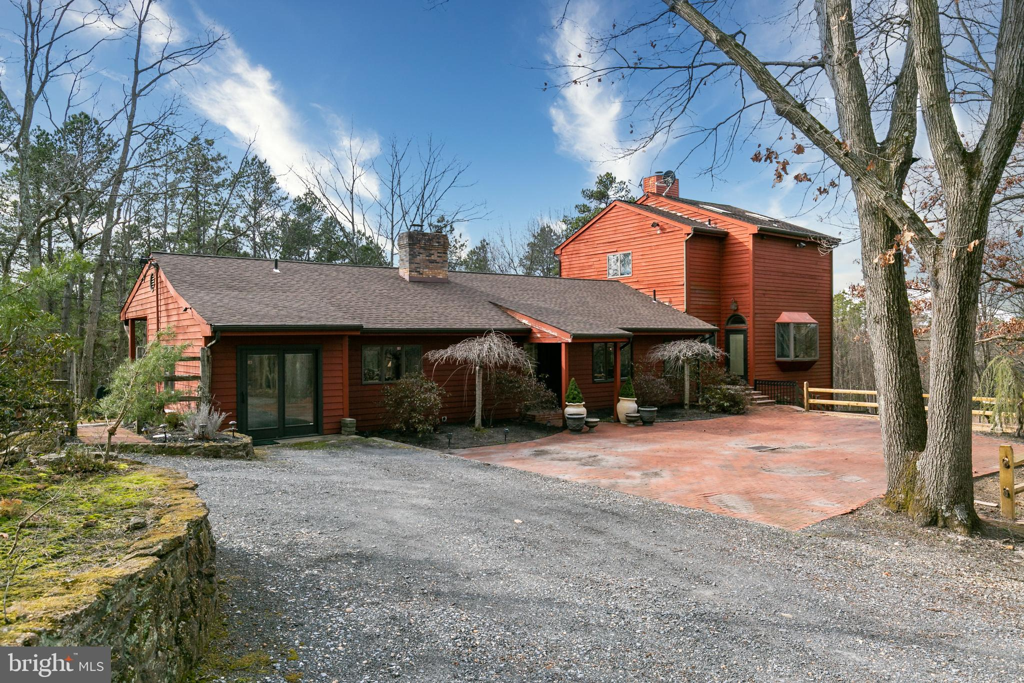 This is your opportunity to own one of the most unique properties in Camden County. Nestled within 14+ acres of complete serenity is this contemporary style home with a view. This 4,000 square foot home has been meticulously maintained and has so much potential for the new owner. Currently the property offers the space to subdivide, making this a builders dream! Or if not looking to subdivide, but instead a buyer who enjoys the outdoors and complete privacy, this is a home for you. You will find hardwood floors throughout majority of the home, including the bedrooms.  With 4/5 bedrooms and 4 bathrooms, you have plenty of space at the current home, but can take advantage of the vast amount of land to extend on the existing if desired. The custom kitchen has tile flooring and counters,  butcher block counter space, sub zero refrigerator and restaurant quality cooking appliances. This is a dream for anyone who enjoys being in the kitchen! And the living space has ample natural lighting and panoramic window views. In the master suite, which is complete with a large updated master bath, you can  really take advantage of the views. From the master bedroom deck you can enjoy a sunrise, fresh air, and a beautiful Philadelphia skyline view. And there is plenty of storage and closet space here, as well as throughout the rest of the home. And back outside boast a custom paver and brick patio, as well as the calming sounds of a small pond and waterfall.  So don't miss this rare opportunity for outdoor space, room to grow and develop, and the ease of enjoying all nature has to offer. And all of this with easy access to major highways, restaurants, shopping, and among award winning schools.